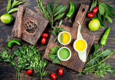 Oils, spices ahd herbs selection. Grape, olive and corn oils fresh herbs, lemons peppers. Top view stock photo