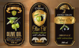 Oilve oil labels. Vector vintage style olive oil labels with decorative plant branches and symbols on wooden background. Elegant gold and black design for olive Stock Photography
