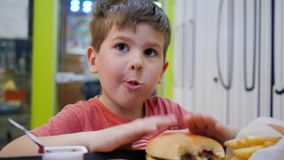 oily food in school cafeteria for lunch small boy eats with appetite in small childrens restaurant beautiful baby