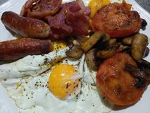 Full English breakfast with sausages bacon mushrooms and tomatoes Royalty Free Stock Photo