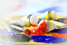 Oily paint. Brush to the palette on the abstract colored background Royalty Free Stock Photo