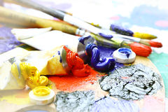 Oily paint. Brush to the palette on the abstract colored background Stock Photo