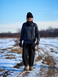 Oin di camminata dell'agricoltore anziano una strada non asfaltata nell'inverno Fotografia Stock