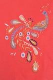 Oiseau brodé sur le tissu de coton rouge Image stock