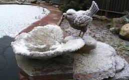 Oiseau décoratif de figurines sur la pierre dans le jardin près de l'étang sous la première neige tombée Photographie stock