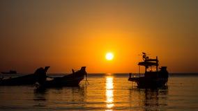 Oiseau et bateau de pêche au coucher du soleil Photos libres de droits