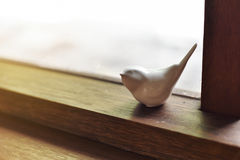 Oiseaux blancs décoratifs sur le châssis de fenêtre dans la maison Image libre de droits