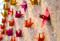 Oiseaux colorés d'origami avec les goupilles en plastique colorées Photographie stock libre de droits