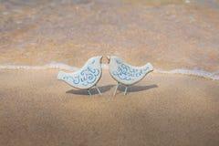 Oiseaux faits main de jouet avec des anneaux de mariage sur la plage Photographie stock