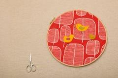 Oiseaux sur la broderie rouge d'arbres dans le cercle près des bouts de fil Photos stock