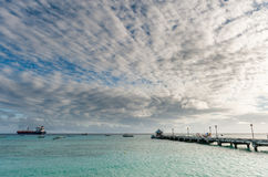 OISTINS,巴巴多斯- 2014年3月15日:与海洋水戏曲天空和油化学制品罐车的迈阿密海滩风景 免版税库存照片