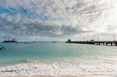 OISTINS,巴巴多斯- 2014年3月15日:与海洋水戏曲天空和油化工罐车,小船的迈阿密海滩风景 库存图片