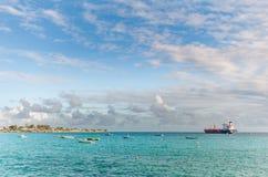 OISTINS,巴巴多斯- 2014年3月15日:与海洋水蓝天和小船,油化学制品罐车的迈阿密海滩风景 免版税库存照片