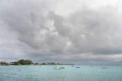 OISTINS,巴巴多斯- 2014年3月15日:迈阿密海滩在有多云风雨如磐的天空和游艇的,小船巴巴多斯在背景中 图库摄影