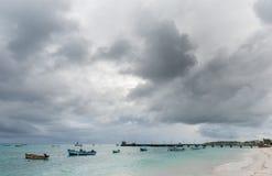 OISTINS,巴巴多斯- 2014年3月15日:迈阿密海滩在有多云风雨如磐的天空和游艇的,小船巴巴多斯在背景中 库存照片