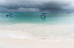 OISTINS,巴巴多斯- 2014年3月15日:迈阿密海滩在有多云风雨如磐的天空和游艇的,小船巴巴多斯在背景中 免版税库存图片