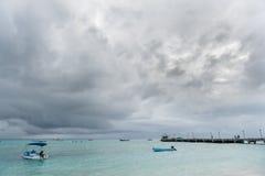 OISTINS,巴巴多斯- 2014年3月15日:迈阿密海滩在有多云风雨如磐的天空和游艇的,小船巴巴多斯在背景中 库存图片