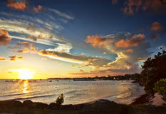 Ηλιοβασίλεμα πέρα από τη δυτική ακτή των Μπαρμπάντος που αντιμετωπίζεται από Oistins Στοκ Εικόνες