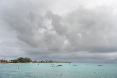 OISTINS, BARBADOS - MARCH 15, 2014: Miami Beach in Barbados with Cloudy Stormy Sky and Yacht, Boats in Background Stock Photography