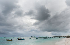OISTINS, BARBADOS - MARCH 15, 2014: Miami Beach in Barbados with Cloudy Stormy Sky and Yacht, Boats in Background Stock Photo