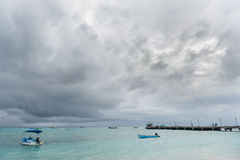 OISTINS, BARBADOS - MARCH 15, 2014: Miami Beach in Barbados with Cloudy Stormy Sky and Yacht, Boats in Background Stock Image