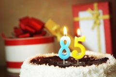 Oitenta e cinco anos de aniversário Bolo com velas e os presentes ardentes Imagens de Stock