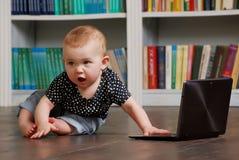 Oito meses de bebê idoso do todler que joga com o PC da tabuleta no assoalho Foto de Stock Royalty Free