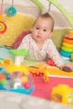 Oito meses de bebê idoso que joga com brinquedos coloridos Imagem de Stock Royalty Free
