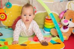 Oito meses de bebê idoso que joga com brinquedos coloridos Imagens de Stock Royalty Free
