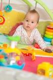 Oito meses de bebê idoso que joga com brinquedos coloridos Imagem de Stock