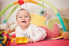 Oito meses de bebê idoso que joga com brinquedos coloridos Fotos de Stock Royalty Free