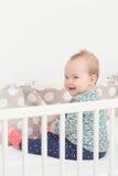 Oito meses de bebê idoso que senta-se em sua cama Imagens de Stock Royalty Free