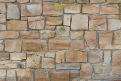 Ojämn gammal sandstenvägg med någon mossa Arkivbild