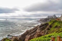 Ojämn kustlinje med den branta klippan och highrisen fotografering för bildbyråer