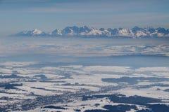 Ojämna snöig höga Tatra maxima ovanför den disiga Podhale handfatet Polen arkivfoto