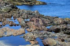 Ojämna stenblock längs kusten av ett blått hav Royaltyfri Fotografi