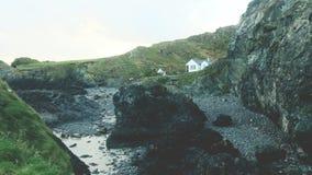Ojämnt landskap & vit byggnad på den Kynance lilla viken, Cornwall royaltyfri foto