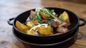 Ojahuri, Ofenkartoffeln mit Fleisch in einer Bratpfanne auf einem Holztisch in einem georgischen Restaurant stock video
