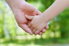 Ojców chwytów ręka dziecko przeciw pięknemu bokeh tłu w słonecznym dniu, szczęśliwy rodzinny pojęcie obraz royalty free