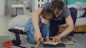 Ojca brodaty mężczyzna jest jego synowi uczący dlaczego używać młoteczkowego jeżdżenia gwóźdź w kawałku drewno wpólnie siedzi na  zbiory