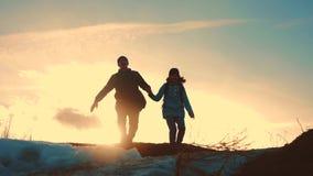 Ojca i córki pracy zespołowej turystów sylwetki pojęcia szczęśliwy rodzinny skok w górę chwyt ręk drużynowy tata dalej i córka zdjęcie wideo
