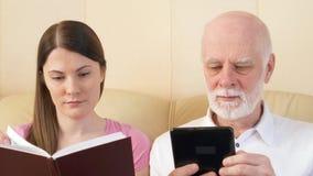 Ojca i córki czytelniczy ebook i fizyczny druk rezerwujemy Pojęcie papier vs cyfrowy czytanie zdjęcie wideo