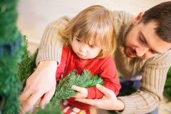 Ojca i córki gromadzić choinka Fotografia Stock