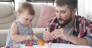 Ojca i dziecka córka bawić się z plasteliną zdjęcie wideo