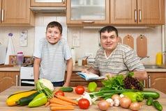 Ojca i dziecka kucharstwa wyboru czytelniczy i książki naczynia Szczęśliwy rodzinny mieć zabawę z owoc i warzywo w domowym kuchen Obrazy Stock