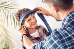 Ojca i małego syna taty siedzący kładzenie na krawacie na chłopiec ono uśmiecha się figlarnie w górę w domu obrazy royalty free