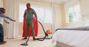 Ojca i syna cleaning pokój z próżniowym cleaner podczas gdy udający być bohaterem 4k zbiory wideo