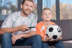 Ojca i syna dopatrywania mecz piłkarski Zdjęcie Royalty Free