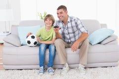 Ojca i syna dopatrywania mecz piłkarski na kanapie Obrazy Royalty Free