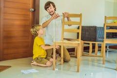Ojca i syna gromadzić meble Chłopiec pomaga jego taty w domu koncepcja szczęśliwa rodzina obrazy stock